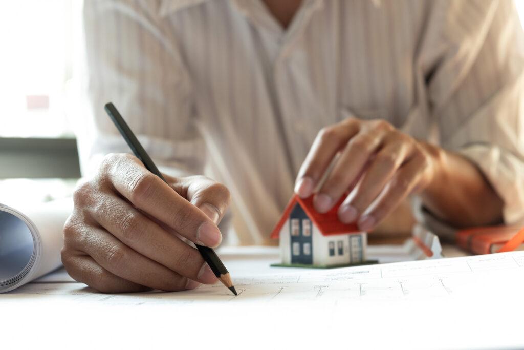 Person mit Stift bei der Immobilienverwaltung