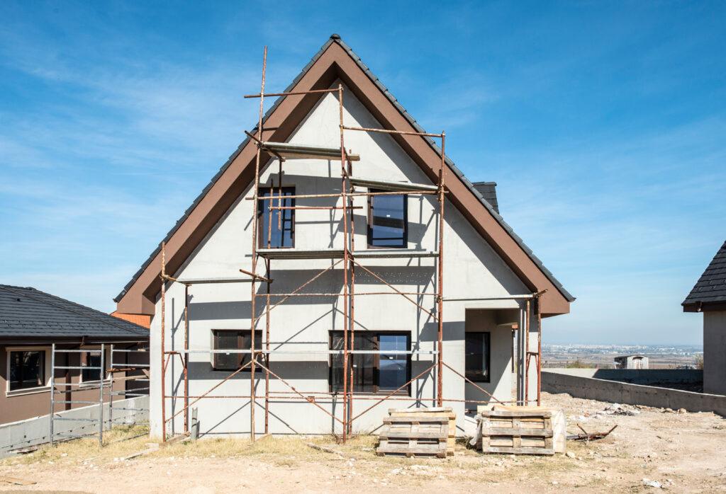 Einfamilienhaus auf dem Landschaft mit blauem Himmel Tapezieren Tapeziere